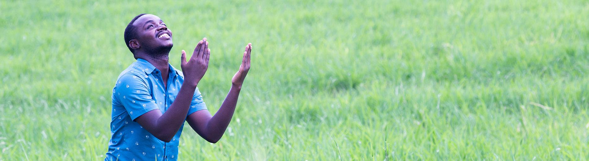 Un homme prie en levant les bras au ciel. Les missions de l'Action Missionnaire : de l'évangélisation au développement spirituel, en passant par la traduction, l'enfance et l'action sociale